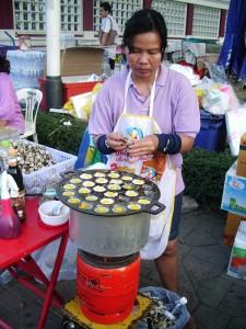 vendor cooking quail eggs in kanom crok hot plate